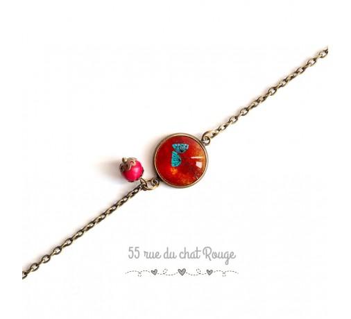 bracelet fine chaîne, coquelicot bleu fond rouge