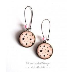 Pendientes, pocas estrellas, fondo de color rosa, joyería para las mujeres de bronce